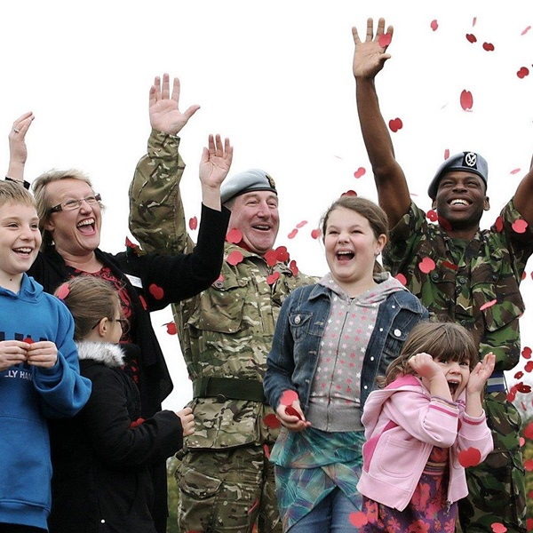Members of the Armed Forces community throwing poppy petals into the air