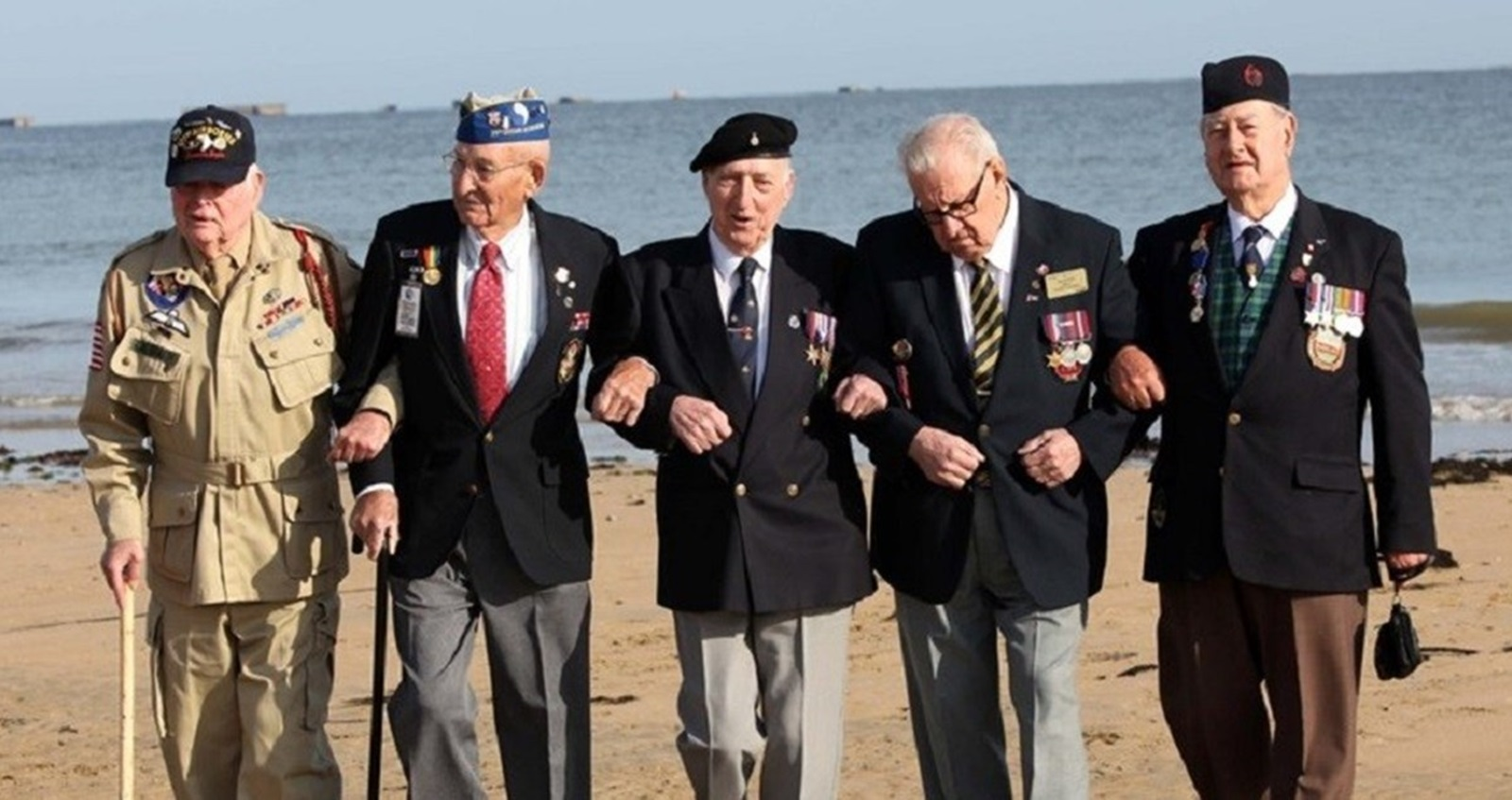 D-Day Veterans walking arm in arm along Normandy beach