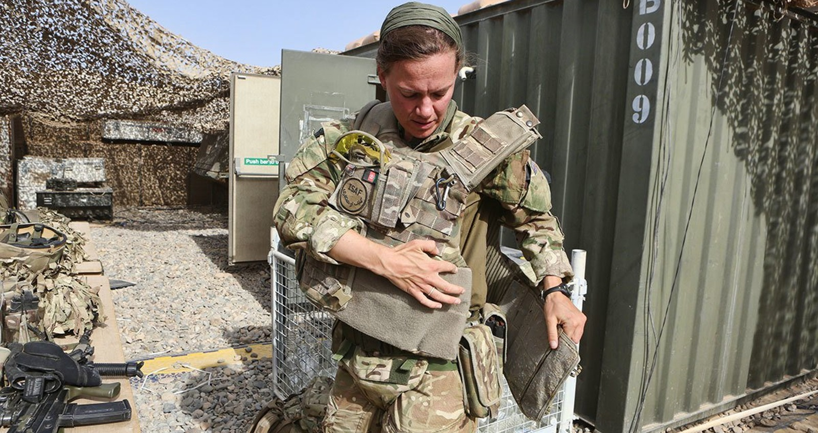 Anna Crossley in Helmand strapping on equipment vest